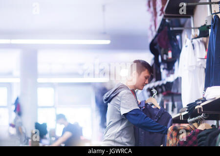 Young male skateboarder looking at shirt in skateboard shop - Stock Photo