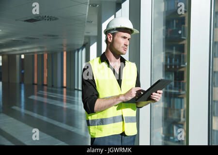 Man wearing hard hat and hi vis vest, looking at digital tablet - Stock Photo