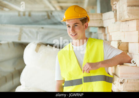 Portrait of man wearing hard hat and hi vis vest, standing beside building materials - Stock Photo