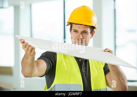 Man wearing hi vis vest, standing in newly constructed space, looking at construction material - Stock Photo