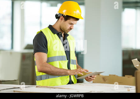 Man wearing hi vis vest, standing in newly constructed space, looking at digital tablet - Stock Photo