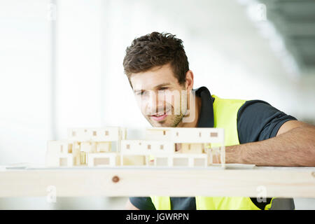 Man wearing hi vis vest, looking at model of building - Stock Photo