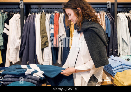 Shopper making decision in clothes shop - Stock Photo