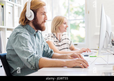 Male and female designers listening to headphones and typing at creative studio  desk - Stock Photo