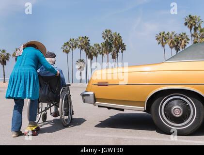 Senior woman pushing husband in wheelchair by vintage car at Venice Beach, California, USA - Stock Photo