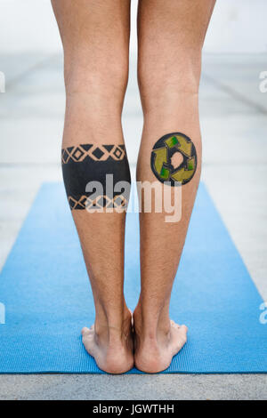 Rear view of tattooed legs of man practicing yoga, standing on yoga mat - Stock Photo