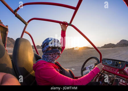 Young woman with head wrapped in scarf driving beach buggy in desert, Hurghada, Al Bahr al Ahmar, Egypt - Stock Photo