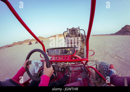 Personal perspective view of two people driving beach buggy in desert, Hurghada, Al Bahr al Ahmar, Egypt - Stock Photo