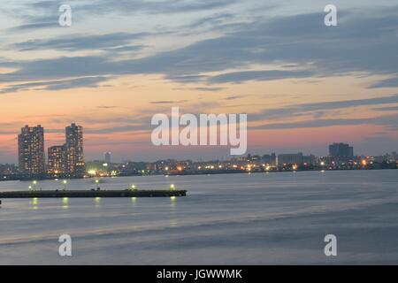 Urban Landscape around bay waters with moving clouds at dusk in horizontal frame - Stock Photo