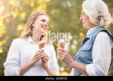 Full of happiness . Smiling happy old woman enjoying the sunny weather outdoors while expressing joy and eating - Stock Photo