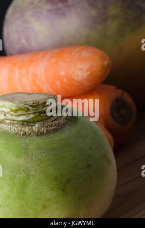 Close up of unwashed; imperfect; raw root vegetables on wooden table, with green turnip in foreground and carrots - Stock Photo