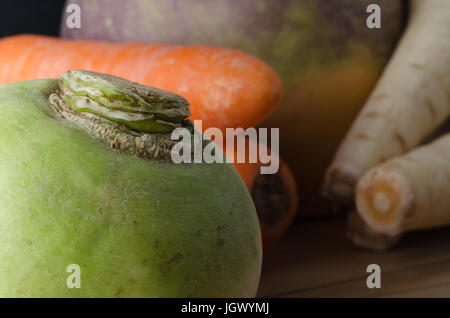 Close up of unwashed, raw root vegetables, grouped on a wood plank table.  Turnip in foreground with carrots, swede - Stock Photo