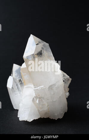 A quartz crystal cluster against a black background. - Stock Photo