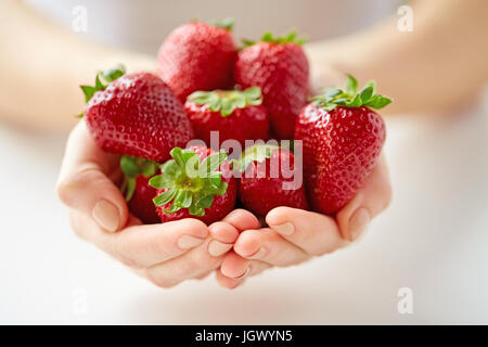 close up of young woman hands holding strawberries - Stock Photo