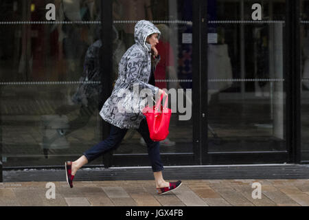 Preston, Lancashire, UK. UK Weather. 11th July, 2017. Woman Late for Work, running in a heavy and persistent rain - Stock Photo