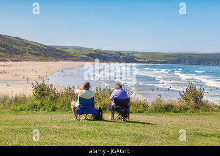 17 June 2017: Woolacombe, North Devon, England, UK - Couple sit overlooking the beach as people enjoy the sunshine - Stock Photo