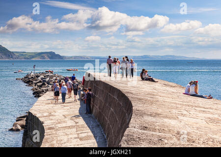 1 July 2017: Lyme Regis, Dorset, England, UK - Visitors enjoying the good weather on The Cobb. Stock Photo