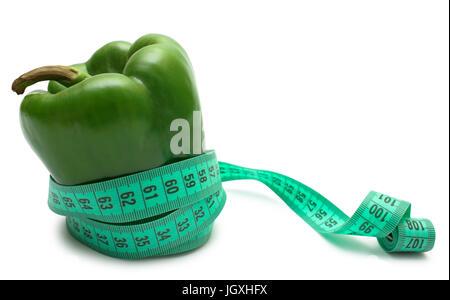 Vegetable diet. Green bell pepper (bulgarian) tighten measuring tape isolated on white. - Stock Photo
