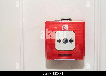 Close up of fire alarm switch in red box on wall - Stock Photo