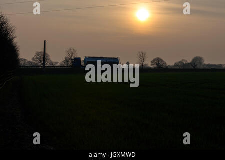Road Tanker travelling at sunset. - Stock Photo