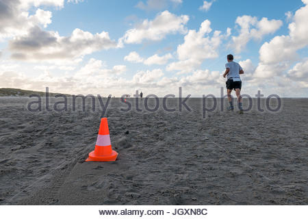 Traffic cone on sand beach with many footsteps man running - Stock Photo