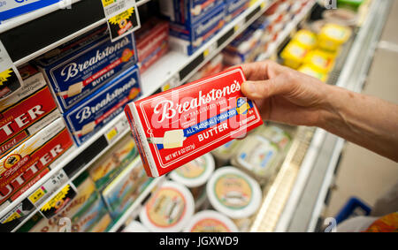 A shopper chooses a package of Breakstones brand butter from a refrigerated case in a supermarket in New York on - Stock Photo