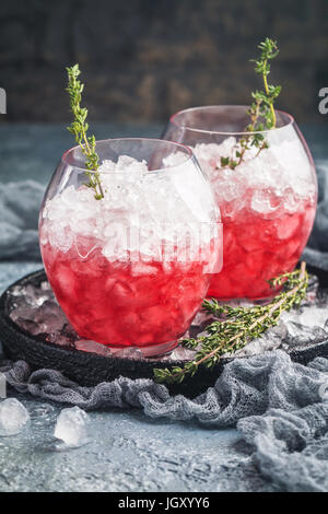 Red drink with berry, ice and thyme. Refreshing summer cocktail in a glass on gray background - Stock Photo