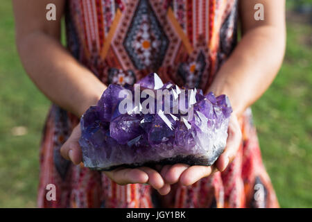 A young woman holds a large cluster of amethyst crystals as they shimmer in the sunlight. - Stock Photo