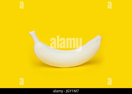Banana painted white on yellow background - Stock Photo