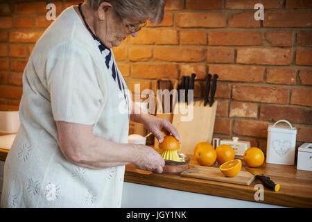 Senior adult woman squeezing oranges - Stock Photo