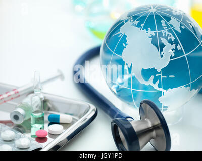 Globe showing the Americas with acoustic stethoscope and surgical tray with medicines - Stock Photo