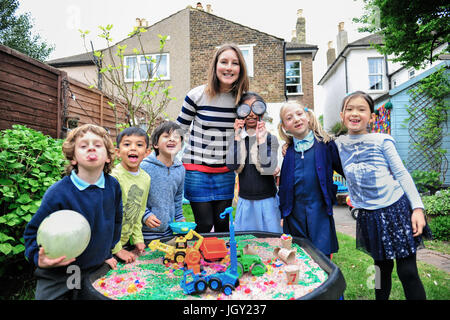 Portrait of childminder and children by sandpit looking at camera smiling - Stock Photo
