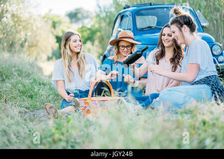 Friends sitting on grass pouring wine, Firenze, Toscana, Italy, Europe - Stock Photo