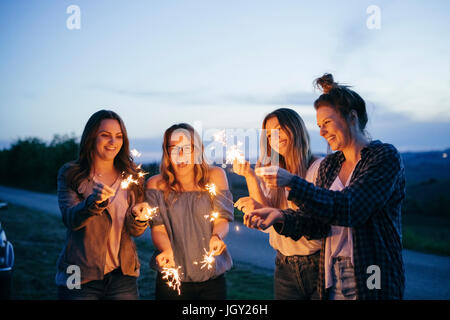 Friends playing with sparklers - Stock Photo