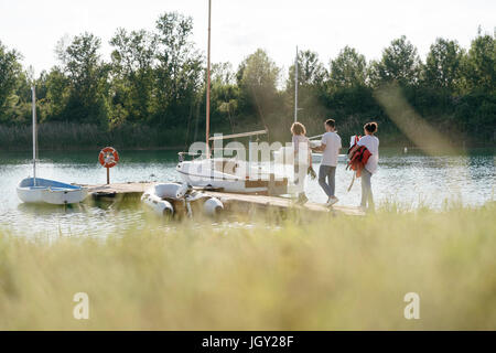 Friends walking towards sailing boat, carrying equipment, long grass in foreground - Stock Photo