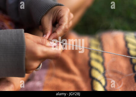 A close-up of a girls hands delicately weaving string while sitting cross-legged on a towel outdoors. - Stock Photo