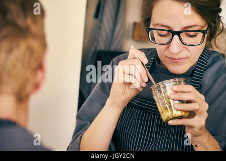 Chef eating food from glass jar - Stock Photo