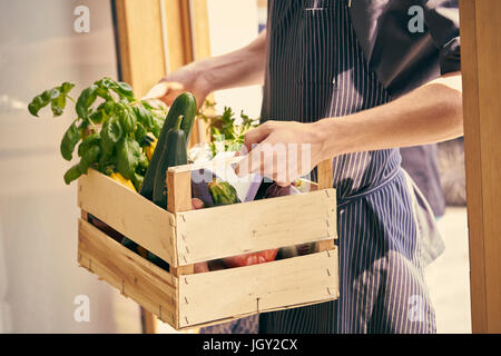 Cropped view of chef carrying crate of vegetables - Stock Photo