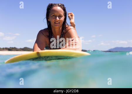 A portrait of a happy young surfer girl in pristine tropical water on a clear summers day in Australia. - Stock Photo