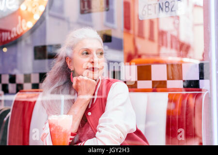 Mature woman in baseball jacket looking through window from 1950's diner - Stock Photo