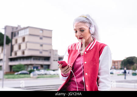 Mature woman in baseball jacket listening to headphones and looking at smartphone - Stock Photo