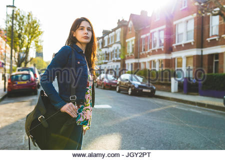 Young woman standing in road, looking down street - Stock Photo
