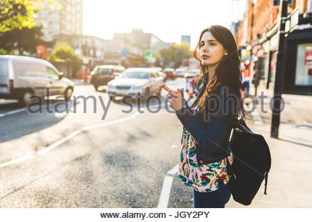 Young woman standing in street, holding smartphone, waiting to cross road - Stock Photo