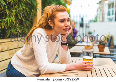 Woman sitting in pub garden, holding pint of beer, bored expression - Stock Photo