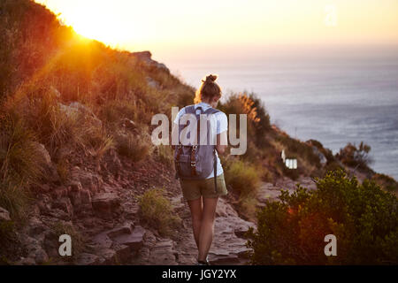 Young woman hiking, rear view, Lions head Mountain, Western Cape, Cape Town, South Africa - Stock Photo