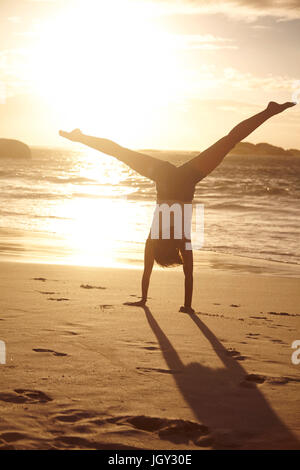 Young woman doing handstand on beach, Schotsche kloof, Western Cape, South Africa, Africa - Stock Photo
