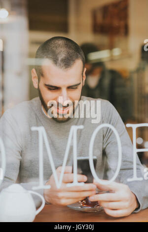 Young man sitting in cafe, using smartphone, view through window - Stock Photo