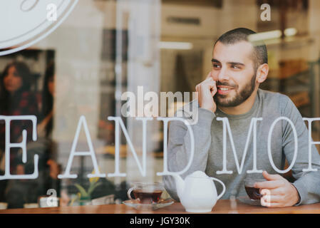 Young man sitting in cafe, view through window - Stock Photo