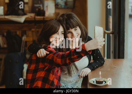 Two female friends, sitting in cafe, taking selfie, using smartphone, cupcake with candle on counter - Stock Photo