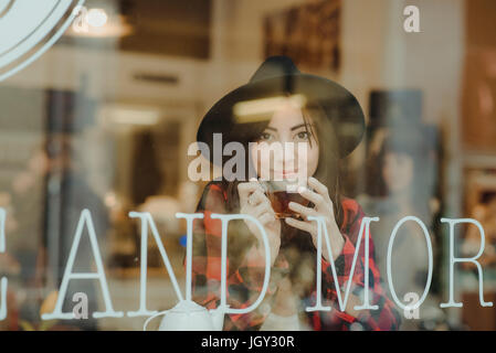 Portrait of young woman sitting in cafe, view through window - Stock Photo